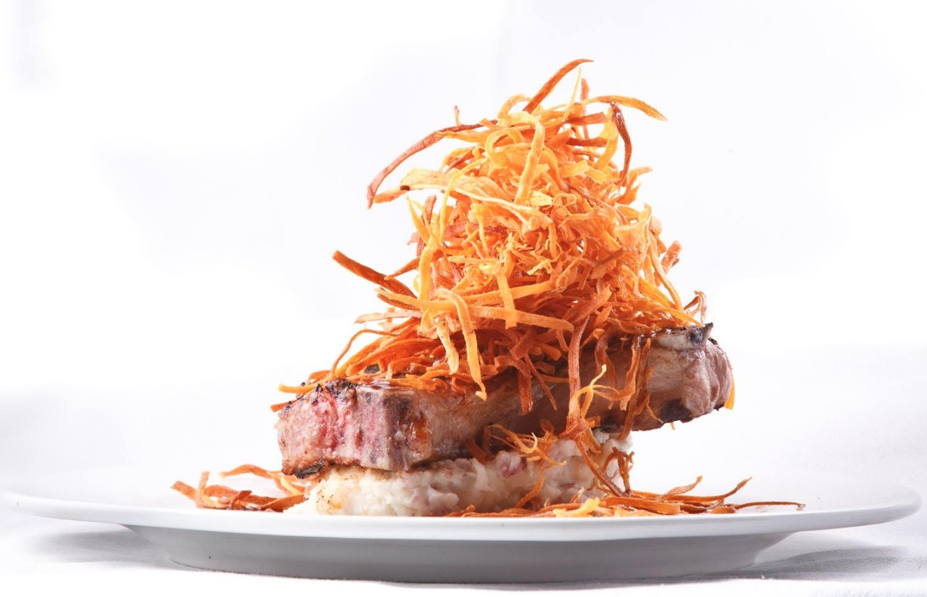Double H Farm pork chop served on a bed mash potatoes and shoestring sweet potato straws. -The Local Restaurant and Catering